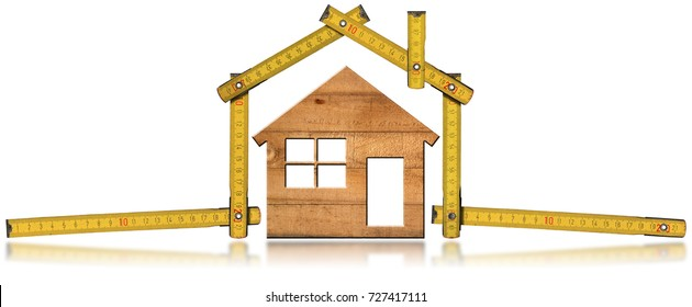 Yellow folding ruler in the shape of house with a wooden model house. Isolated on white background. Construction industry concept
