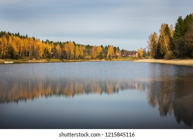 Yellow foliage trees and blue sky with clouds reflected in the water