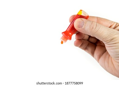 Yellow food coloring bottle being squeezed at an anglr isolated over white