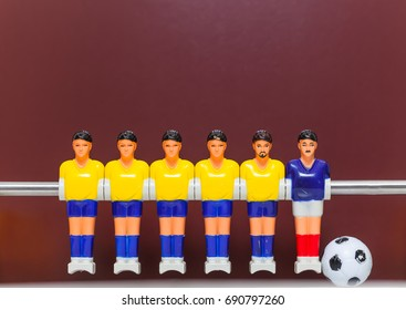 Yellow foosball table players team on a brown background