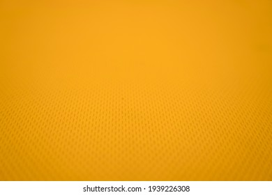 Yellow football jersey clothing fabric texture sports wear background, close up. Sport Clothing Fabric Texture Background. Top View of Cloth Textile Surface. Yellow Football Shirt.