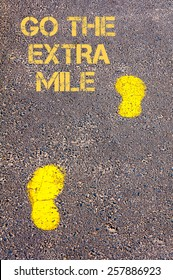 Yellow footsteps on sidewalk.Go The Extra Mile message.Concept image