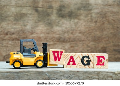 Yellow forklift hold block w to complete word wage on wood background