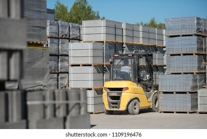 Yellow forklift moving around warehouse yard lifting pallets of concrete blocks. Concrete block's manufacture warehouse center.