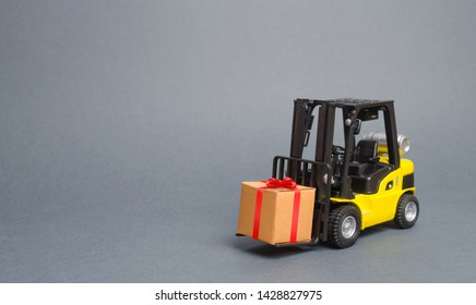 Yellow forklift truck carries a gift with a red bow. Purchase and delivery of a present. retail, discounts and contests. sweepstakes and contest promotions. Increase sales and attract new customers.