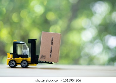 Yellow forklift truck with miniature cardboard box. production of goods. transportation, storage of cargo. Freight shipping, delivery of goods. logistics industries.
