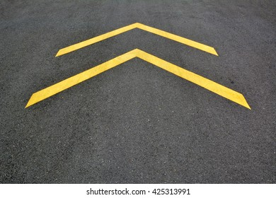 """Yellow """"forward"""" symbols in the middle of the asphalt road."""