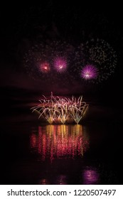 Yellow fountain, violet stars with  bright glitter in rich fireworks over Brno's Dam with lake reflection