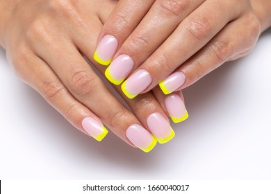 yellow french manicure, sparkles on short square nails closeup on a white background