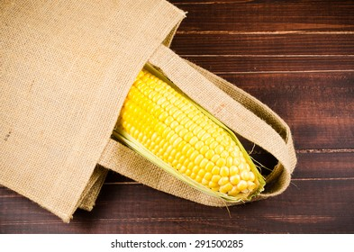 Yellow fresh corn in sack bag on wooden board background