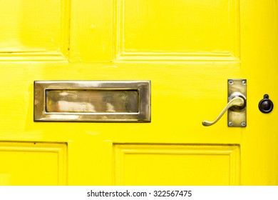 A yellow front door with a metal letterbox and handle