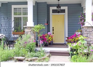 Gelbe Haustür eines kleinen Hauses in den Vororten von Kanada. Attraktive und farbenprächtige Veranda, umgeben von Blumen und Jahresblumen im Sommer.