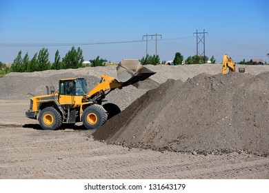 A yellow Front end loader excavating a large hole