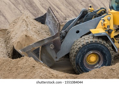 Yellow front loader tractor in strip sand mine. Open pit sand mining. Natural resources excavation.