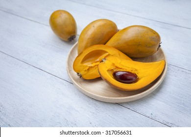 Yellow fruit on wooden tray, Fresh Pouteria campechiana fruit