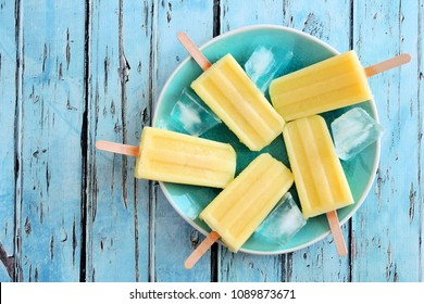 Yellow fruit popsicles on a plate. Top view over a blue wood background.