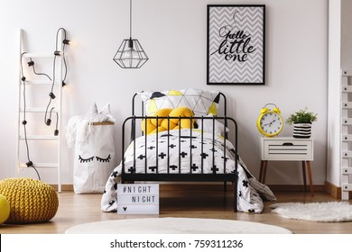 Yellow funny clock and plant on nightstand in white child's bedroom with yellow pouf on wooden floor