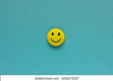Yellow funny smiley face on blue background. Positive mood concept