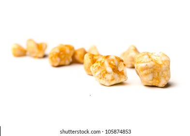 Yellow gall stones from a persons gall bladder over white background