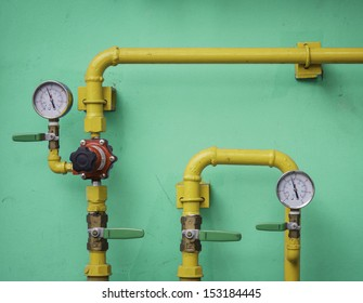 Yellow gas meter against blue wall