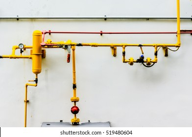 Yellow gas pipe in front of residential building wall, gas pipe in front of residential building wall