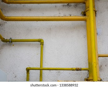 Yellow gas pipes on old dirty building wall close up shot.