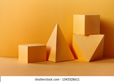Yellow geometrical figures still life composition. Three-dimensional prism pyramid rectangular cube objects on yellow background. Platonic solids figures, simplicity concept