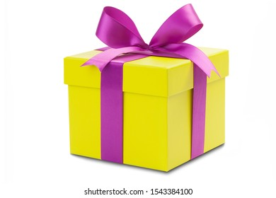 Yellow gift box with purple ribbon isolated in front of white background