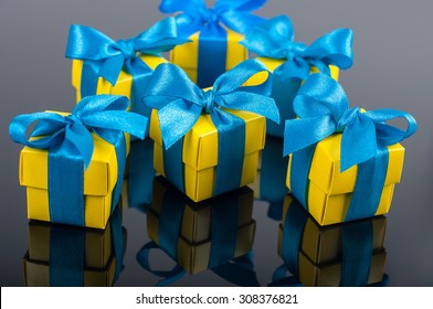 Yellow gift boxes with blue satin ribbons on the mirror dark background