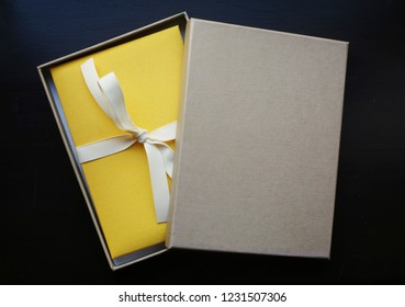 Yellow gift / photoalbum in a craft box with a white ribbon on a dark black background / merry christmas, birthday, anniversary, happy new year celebration / decoration or poster design template