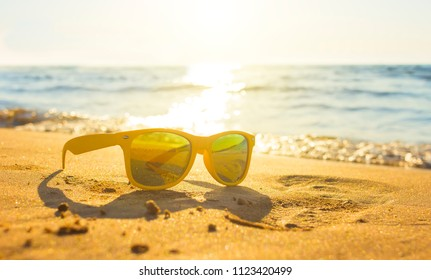 Yellow glasses the sea sand, sunglasses with beautiful sea scenery. sunglasses are reflected in the Golden wet sand as in the mirror
