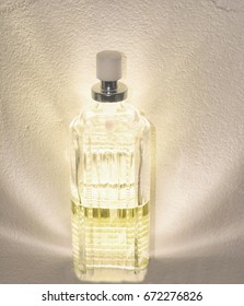 A yellow glowing perfume bottle on a texture background.