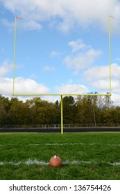 Yellow Goal Posts and Football on American Football Field
