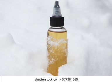 yellow (gold) bottle with liquid for electronic cigarette surrounded snowflakes