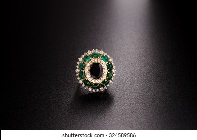 yellow gold diamond ring with emeralds and sapphire isolated on black background