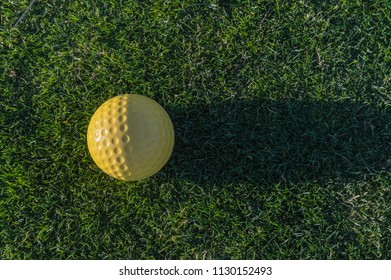 Yellow golf ball with its shadow on the grass of a course near Santa Cruz on the island of Tenerife