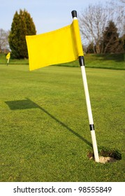 Yellow Golf Flag in Hole on Golf Course Green
