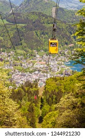Yellow gondola of Zwoelferhorn Seilbahn (cable way) travel up and down alpine peak with a view of village St.Gilgen and Wolfgangsee lake, Salzburg land, Austria