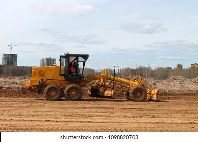 yellow grader levels the ground for construction