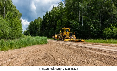 Yellow grader working on the rural road.