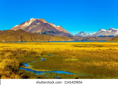 The yellow grass field with streams from underground sources. Trip to the Argentine Patagonia. The private hacienda are surrounded by distant mountains. The concept of exotic and active tourism