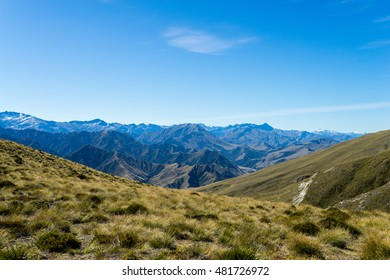 Yellow grass fields and hills with sharp steep mountains in the background.