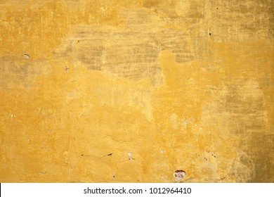Yellow and Gray Dirty Plaster Wall, With Falling Off Flakes Of Paint. Rough Surface. Old Weathered Painted Background Texture. Vintage Timber Background. Peeled Plaster Brickwall