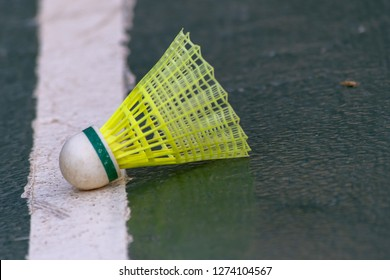 A yellow and green badminton shuttlecock (birdie) lands on the line and is in!