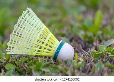 A yellow and green badminton shuttlecock (birdie) on a green grass background.