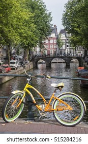 Yellow and green bike with buildings and old bridge as background in Amsterdam