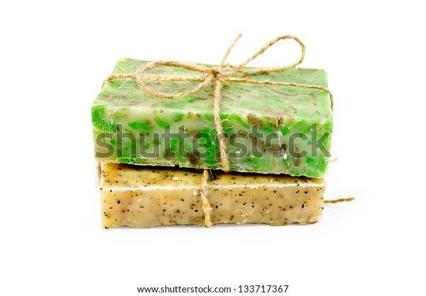 Yellow and green handmade soap, tied with string isolated on white background