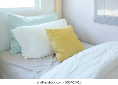 Yellow and green pillow on tiny bed in kid bedroom interior
