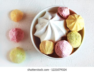 Yellow, green and pink meringues in a white bowl on a white background