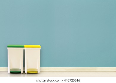 Yellow and Green Recycle Bin on the floor with blue wall background